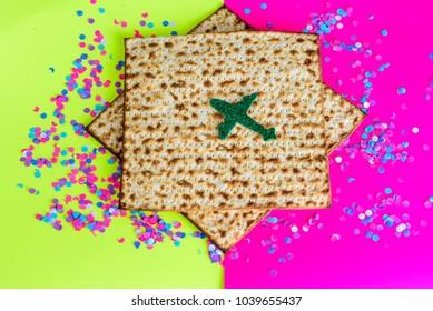 Matzah, airplane and confetti on  bright celebrating background.Passover Jewish holidays vacation travel concept.