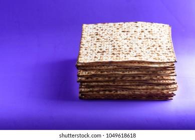 Matzah on ultra violet trendy background. Matza -Jewish traditional Passover unleavened  bread. Pesach celebration symbol.