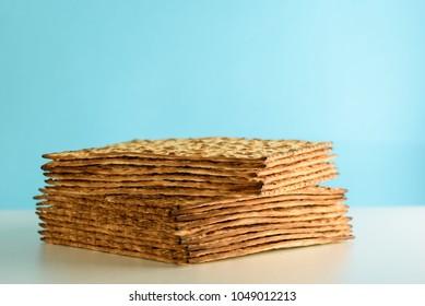 Matzah on white table over  blue background.Matza -Jewish traditional Passover unleavened  bread. Pesach celebration symbol.