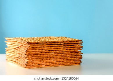 Matzah on white table over  blue background.Matza -Jewish traditional Passover unleavened  bread. Pesach celebration symbol.