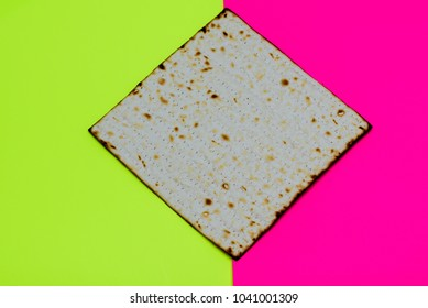 Matzah on yellow pink modern background.Matza -Jewish traditional Passover unleavened  bread. Pesach celebration symbol.