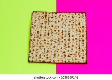 Matzah on yellow pink trendy background.Matza -Jewish traditional Passover unleavened  bread. Pesach celebration symbol.