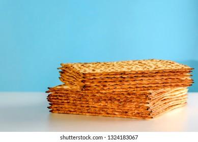 Matzah Passover celebration symbol on white table over blue background. Matza -Jewish traditional Pesach unleavened  bread .