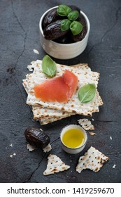 Matzo bread with date fruits and salmon fillet over grey stone background, vertical shot