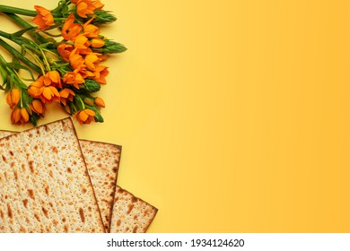 Matzo and flowers on yllow background, top view. Passover (Pesach) Seder Pesah celebration concept (jewish Passover holiday).