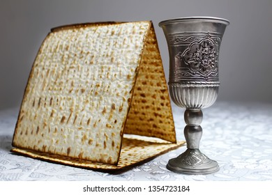 Matzo (Matzah or Matzo) and vintage wine glass. Symbolic foods for Passover. Passover (Pesach or Pesah) - Jewish holiday
