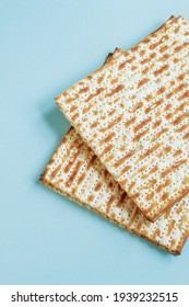 Matzo on blue background. Happy Passover concept. Traditional Jewish food for Pesach. Vertical photo.