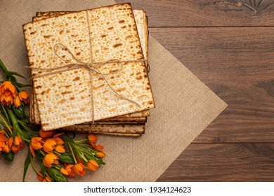 Matzo and orange flowers on a canvas napkin. Wood background. Passover (Pesach) Seder Pesah celebration concept (jewish Passover holiday). Top vew