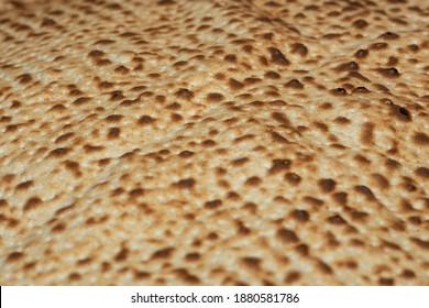 Matzo Textur, eine Draufsicht eines Stücks von traditionellem Weizentrockenbrot serviert auf Hebräischem Pessach. gebackener matzo, matzoische Textur, Hintergrund.