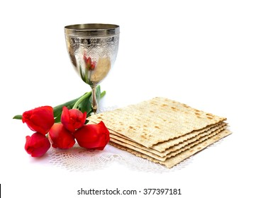 Matzo, wine and red tulips for passover celebration on white background.