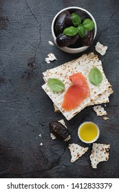 Matzoh bread with salmon, ripe dates and fresh green basil. Flatlay on a grey stone background, vertical shot with space