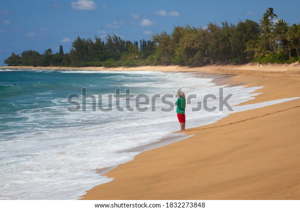 Maui beach in Hawaii. An unidentified person stands with his back in the waves of the sea on the beach on the Hawaiian island of Maui. Concept relaxing rest