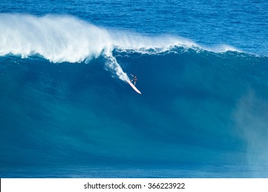 """MAUI, HI - JANUARY 16 2016: Professional surfer rides a giant wave at the legendary big wave surf break known as """"Jaws"""" on one the largest swells of the year."""