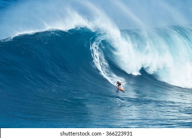 """MAUI, HI - JANUARY 16 2016: Professional surfer Tyler Larronde rides a giant wave at the legendary big wave surf break known as """"Jaws"""" on one the largest swells of the year."""