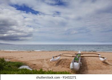 Maui outrigger adventure canoe on sandy ocean beach