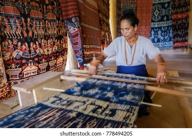 Mauliru, Haumara, East Sumba, East Nusa Tenggara, Indonesia - November 2017 : A Sumbanese woman holding up the tradition of ikat weaving