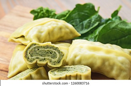 A lot of Maultaschen with fresh green spinach leaf. Maultaschen is a traditional German dish that originated in the region of Swabia.
