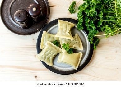 maultaschen, German, traditional dumplings on a plate, next to fresh parsley, salt shaker and pepper pot, view from the top