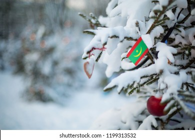 Mauritania flag. Christmas background outdoor. Christmas tree covered with snow and decorations and Mauritania flag. New Year / Christmas holiday greeting card.