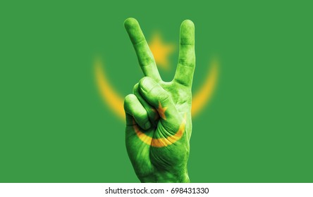 Mauritania national flag painted onto a male hand showing a victory, peace, strength sign