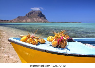 MAURITIUS: A boat with coconuts on Benitiers Island with the Morne Braband in the background