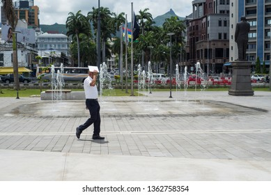 Mauritius / Port Louis - 08.01.2019: Image of local man in a hot tropical day, walking on city's promenade.