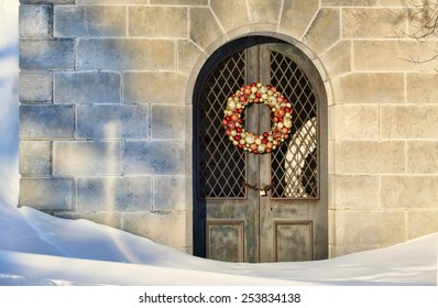 Mausoleum with a Christmas wreath on the door sits silently in the deep snows of Winter.