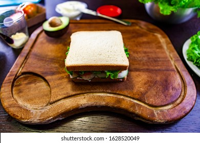 Maxi toast stuffed with salad and tomato on wooden cutting board. Avocado cut in two