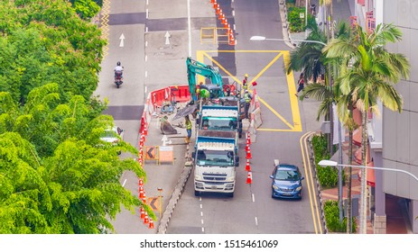 Maxwell road, Singapore - 15 July, 2019: View of men working heavy equipment and workers seen from above, workers scurry around rebar frame, Site in China Town, Singapore.