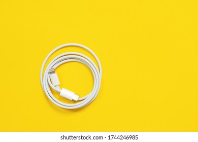May 01, 2020, Rostov, Russia: White Apple wire lightning to usb type c, arranged in round skein on bright yellow background. Indoors, isolated, copy space.