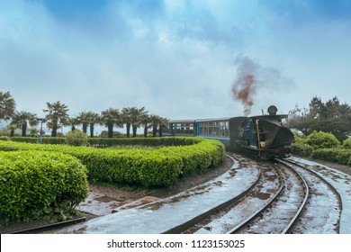 May 01,2017.The Darjeeling Himalayan Railway, also known as the Toy Train, is a 2 ft narrow gauge railway,is entering to the Batasia loop,Darjeeling, west bengal, India. after a heavy rainfall.