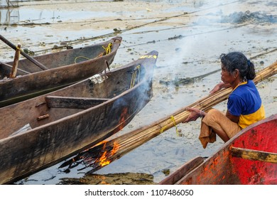 May 1 2018 - Myeik Archipelago, Myanmar. Moken woman repairing canoe on beach