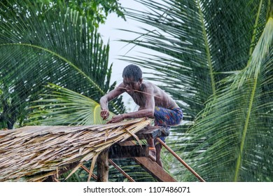 May 1 2018 - Myeik Archipelago, Myanmar. Moken man thatching a hut in the driving rain