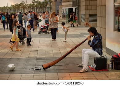 May 11, 2017 -Barcelona, SPAIN- street musician playing the didgeridoo, wind instrument of the Australian aboriginal peoples. The scene takes place near the Olympic port.