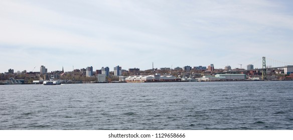 May 12, 2018 - Dartmouth, Nova Scotia: Halifax Harbour from the Dartmouth side, with a ferry crossing, naval shipyard and the MacDonald bridge