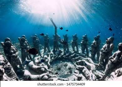 May 12, 2019. Gili Meno, Indonesia. Woman freediver with fins dive near underwater statues. Underwater tourism in the ocean.