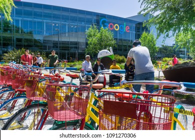 May 13, 2018 Mountain View / CA / USA - A group of people taking a photo at Google's main headquarters in Silicon Valley; colorful bicycles in the foreground;