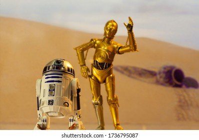 MAY 13 2020: Recreation of a scene from Star Wars A New Hope depicting droids C-3PO and R2D2 on the desert planet of Tatooine with escape pod - Hasbro action Figure