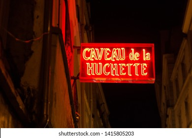 """May 15 2019. Beautiful night shot of the red """"Caveau de la huchette"""" sign in Paris (France). Jazz club in the Latin Quarter. The building exists since the 16th century. Neon light. Seen in La La Land."""