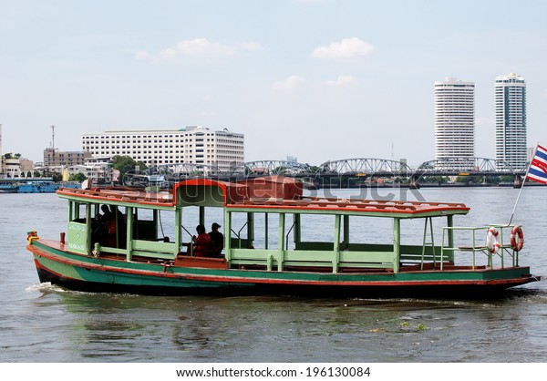 May 16, 2014: Bangkok Thailand. Transport boat as cheap and essential choice in everyday life of Thais near Chaopraya river, smooth water surface with private homes and business area in the background