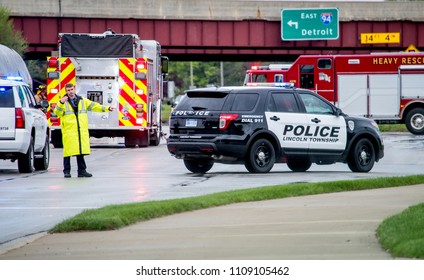 May 18 2018 Stevensville MI USA; A police man in rain gear directs traffic at the scene of a bad accident, with fire trucks waiting behind him