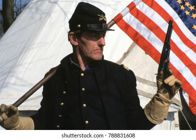 May 18th 1996 a member of the American Civil War Society wears the uniform of a US Cavalry Officer 1876 he is holding a United States flag and is armed with a Colt Army revolver. Photo taken in Kent.