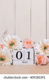 May 1st. Happy May Day white block wood calendar decorated with spring flowers on wood table.