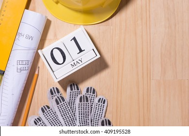 May 1st. Image of may 1 white blocks wooden calendar with construction tools on the table. International Workers' Day. Labor day concept. Copy space view from above