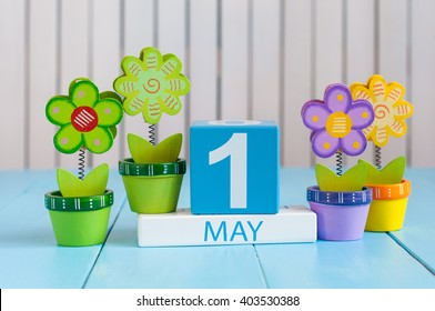 May 1st. Image of may 1 wooden color calendar on white background with flowers. Spring day, empty space for text.  International Workers' Day