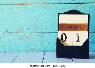 May 1st. Image of may 1 wooden calendar over blue wooden background. Spring day,  International Workers' Day, Happy May Day . room for text