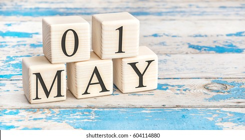 May 1st. Wooden cubes with date of 1 May on old blue wooden background.