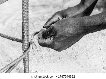 May 2, 2021 Naranjal Arriba, Dominican Republic. Dramatic black and white image of a haitian construction worker tying rebar on a construction site high in the Mountains of the Caribbean.