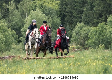 May 20, 2018. Russia, Moscow. Mozhaisk. Parfors hunting in fields of Moscow area. Jump through an obstacle group of riders