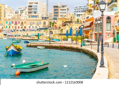 May 20, 2018. St. Julian. Malta. Beautiful old town of St. Julian on the island of Malta with colourful boats, bay, promenade and a statue of a fisherman with a cat and a fish.